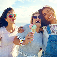 Three women having fun eating ice cream at the beach